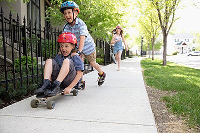 Playful boy pushing brother on skateboard on neighborhood sidewalk - p1192m2000197 by Hero Images