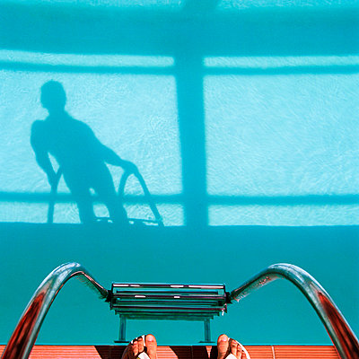 Man Holding On To Railing, Watching His Shadow Inside Pool - p1531m2264183 by Jens Lucking