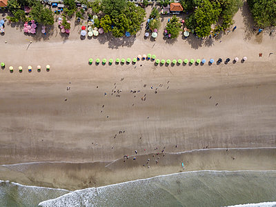 Bali, Kuta Beach, row of beach umbrellas and people on the beach, aerial view - p300m2070213 by Konstantin Trubavin