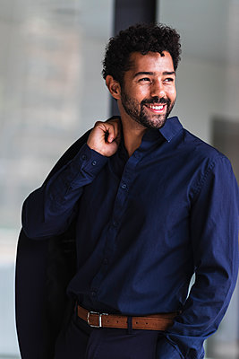 Smiling businessman holding blazer while standing in city - p300m2226450 by NOVELLIMAGE
