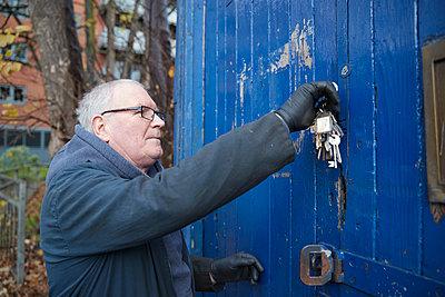 Caucasian male technician with keys opening door of workshop - p300m2277074 by Pete Muller