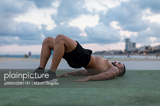 Barechested muscular man doing workout outdoors - p300m2081151 by Mauro Grigollo