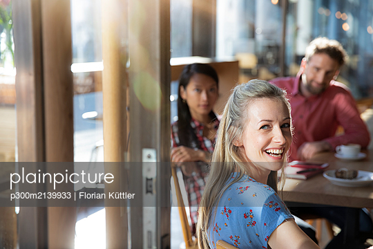 Portrait of happy woman with friends in a cafe - p300m2139933 by Florian Küttler