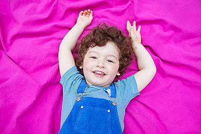 Junge liegt auf pinker Decke - p045m1440057 von Jasmin Sander