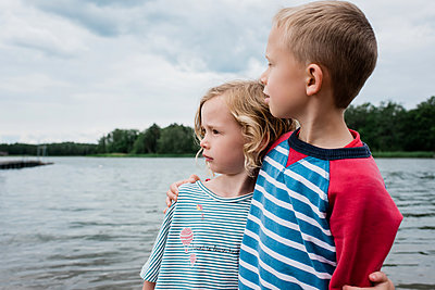 brother and sister hugging looking out to sea at the beach in summer - p1166m2129968 by Cavan Images
