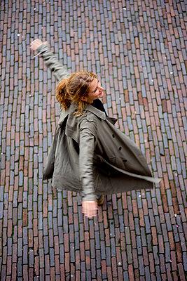 Junge Frau dreht sich auf dem Kopfsteinpflaster - p1212m1492149 von harry + lidy
