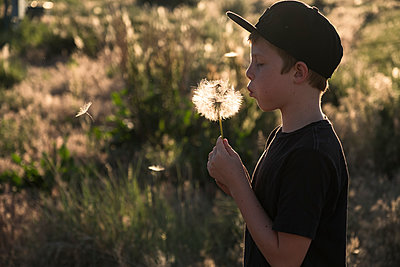Child Blowing Dandilion Weeds - p1262m1444503 by Maryanne Gobble