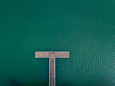 Two friends sitting side by side on jetty, Valdemurio Reservoir, Asturias, Spain - p300m2180374 by Daniel González