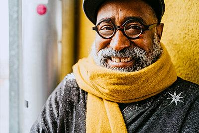 Portrait of smiling senior man wearing yellow scarf - p426m2279760 by Maskot