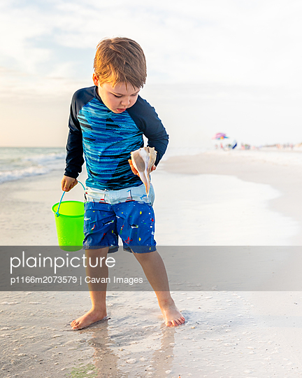Young Boy on the Beach Looking at a Seashell with Wonder - p1166m2073579 by Cavan Images