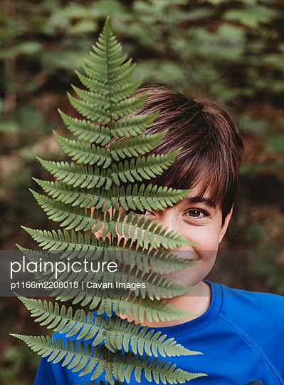 Portrait of young smiling boy covering half his face with fern leaf. - p1166m2208018 by Cavan Images
