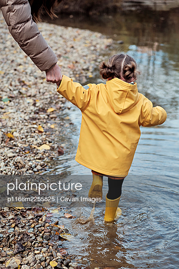 A 2-year-old girl with her mother on the bank of a river - p1166m2255825 by Cavan Images