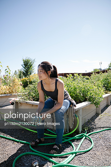 Young woman with gardening gloves in sunny community garden - p1192m2130072 by Hero Images