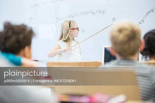 Schoolgirl explaining formula at whiteboard in class - p300m2003914 by Fotoagentur WESTEND61