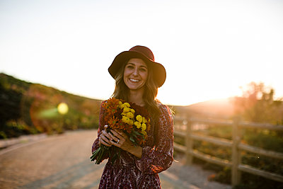Young woman holding flowers, smiling with sun flare in SoCal - p1166m2095780 by Cavan Images