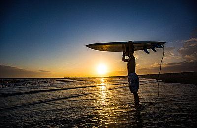 Junge mit Surfbrett bei Sonnenuntergang - p1211m1531903 von Danny Weiss