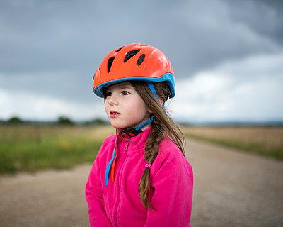 Girl wearing orange cycling helmet looking sideways - p300m2206537 by Biederbick&Rumpf