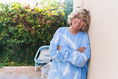 Mature woman with arms crossed leaning on wall at back yard - p300m2276010 by Manu Padilla Photo