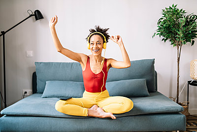 Young woman enjoying music over headphones sitting on sofa at home - p300m2277250 by COROIMAGE