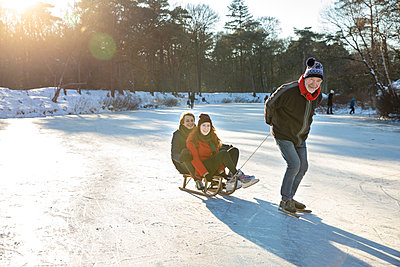 Senior man ice-skating while pulling couple on sled over frozen lake - p300m2287633 by Frank van Delft