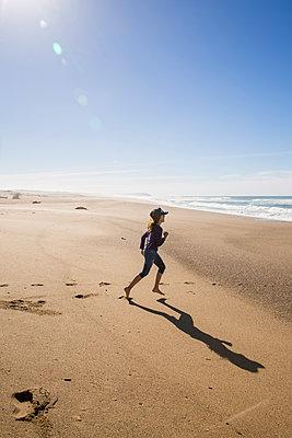 Girl running along the beach, Abbotts Lagoon, California, USA - p756m2053381 by Bénédicte Lassalle