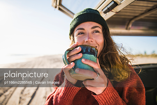 Young woman enjoying cup of coffee in the morning beach car camping - p1166m2285565 by Cavan Images