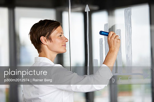 Businesswoman drawing bar chart at glass pane in office - p300m2012974 von Rainer Berg