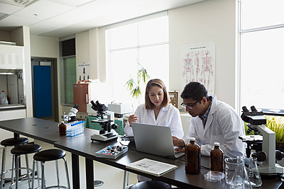 College students conducting scientific experiment at laptop in laboratory - p1192m1145697 by Hero Images