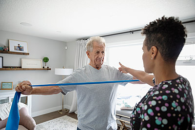 Home healthcare nurse helping senior man exercise with resistance band - p1192m2109840 by Hero Images