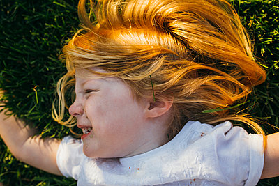 Profile of Little Girl with Red Hair Laying in the Grass and Smiling - p1238m1042074 by Amanda Voelker