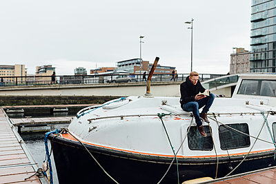 Ireland, Dublin, young man sitting on a motorboat reading a book - p300m1120634f by Boy photography