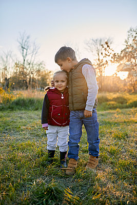 Affectionate brother and sister standing on a meadow at sunset - p300m2189627 by Zeljko Dangubic