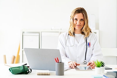 Blond female medical professional sitting with tablet and laptop at desk - p300m2265436 by Giorgio Fochesato