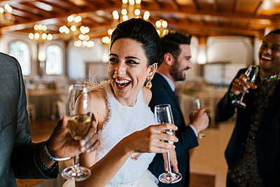 Male and female friends drinking champagne and laughing at banquet - p300m2275029 by Ezequiel Giménez