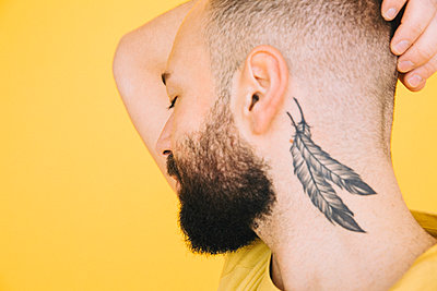 Close-up of neck tattoo on man against yellow background - p426m2205126 by Maskot