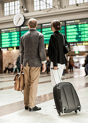Business people with luggage standing on railway station - p426m844669f by Maskot