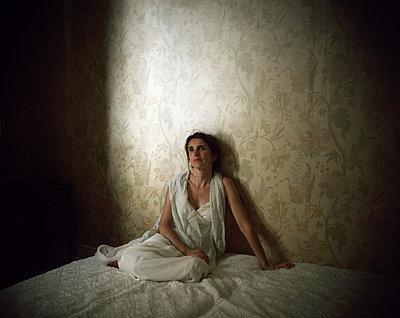 Woman sitting on bed - p945m2126798 by aurelia frey
