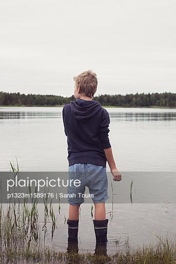 boy by a lake - p1323m1589176 von Sarah Toure