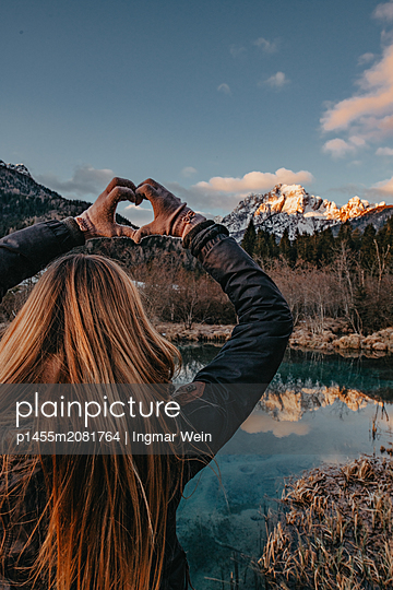 Woman enjoys a early morning sunrise at the Zelenci Natural Reserve in Slovenia - p1455m2081764 by Ingmar Wein