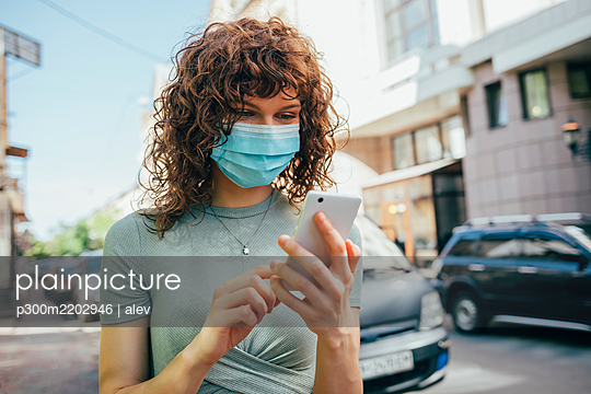 Woman wearing protective mask and using smartphone in city - p300m2202946 by alev