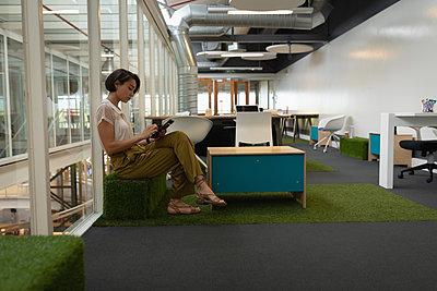 Businesswoman using digital tablet in office - p1315m2091119 by Wavebreak
