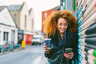 Ireland, Dublin, smiling woman with coffee to go hearing music with smartphone and earphones - p300m1101308f by Boy photography