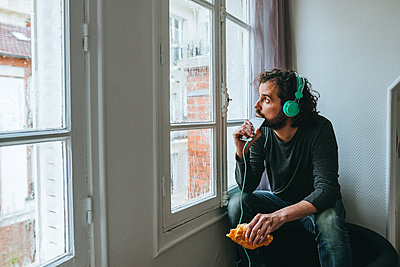 Man listening music with headphones and smartphone at home - p300m1449886 by Kiko Jimenez