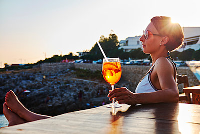 Italy, Santa Caterina, woman relaxing on promenade with glass of Spritz at sunset - p300m1505319 by Dirk Kittelberger
