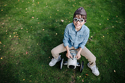 Little boy having fun, riding vintage toy car in the garden - p300m2166679 by Kniel Synnatzschke