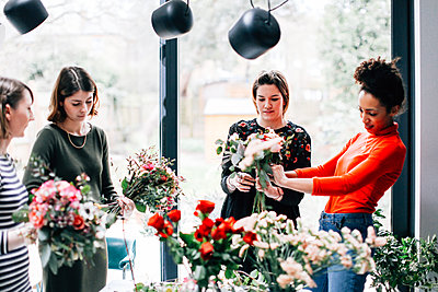 Florist and students arranging bouquets at flower arranging workshop - p429m1418064 by Alys Tomlinson