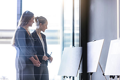 Businesswomen discussing ideas in office - p429m2004421 by suedhang photography