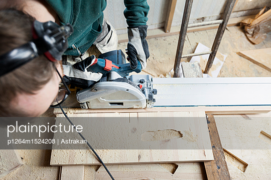 Man using power tool while renovating old attic - p1264m1524208 by Astrakan