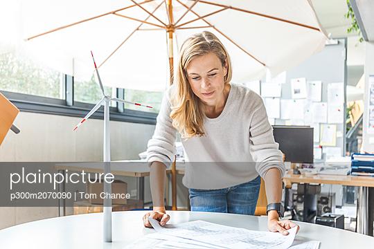 plainpicture - plainpicture p300m2070090 - Woman in office working on ... - DEEPOL by plainpicture/Tom Chance