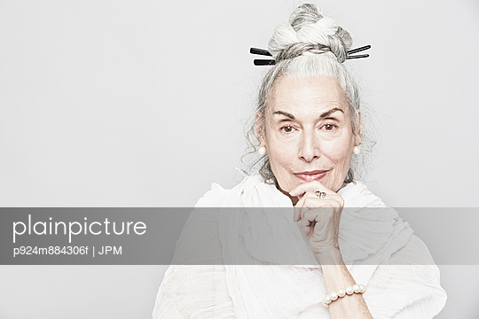 Studio portrait of sophisticated senior woman with hand on chin - p924m884306f by JPM